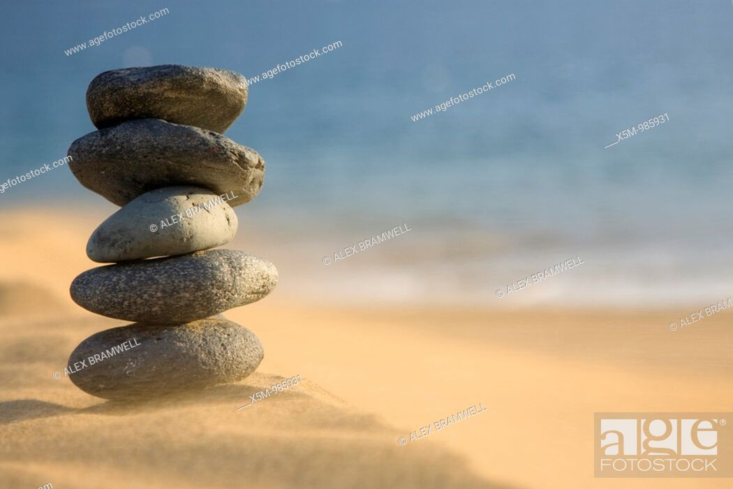 Stock Photo: Stack of volcanic pebbles on a beach with blowing sand.