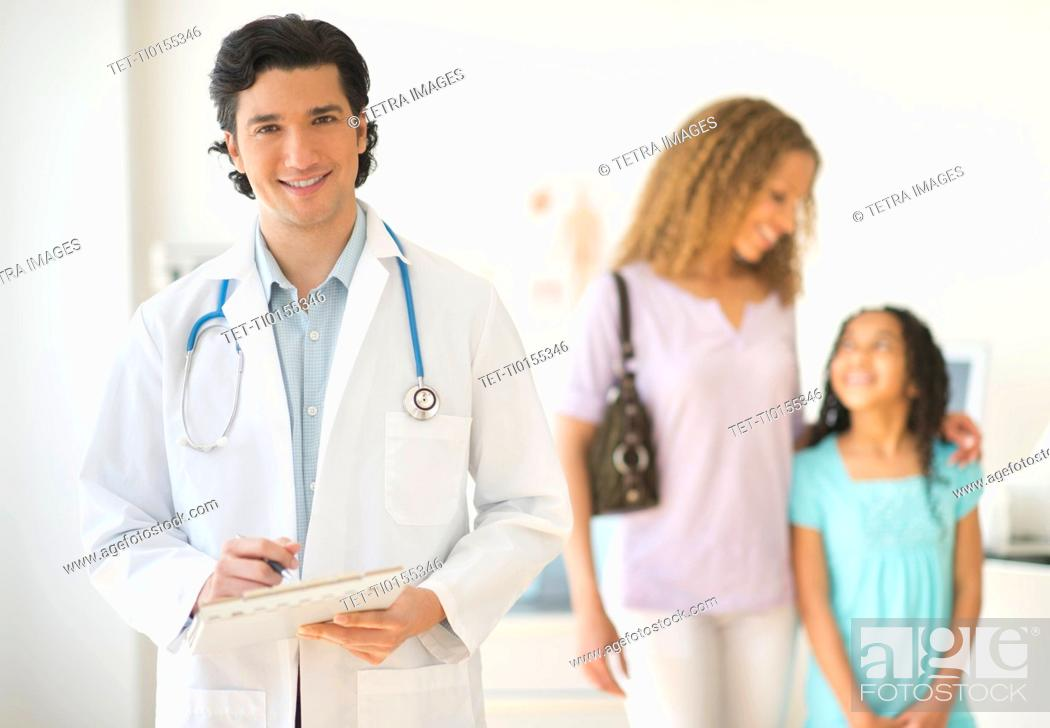 Stock Photo: Doctor with patients woman and girl aged 12-13 in office.