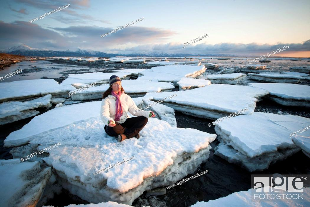 Imagen: Woman practicing meditation on ice chunks stacked against the Homer Spit, Southcentral Alaska.