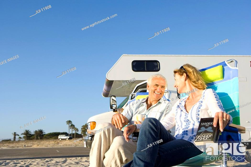 Stock Photo: Mature couple by motor home on beach, smiling at each other, low angle view.