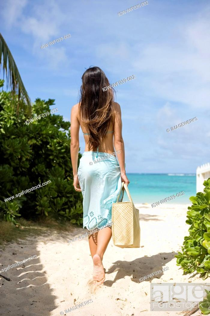 Stock Photo: A woman walking on beach.