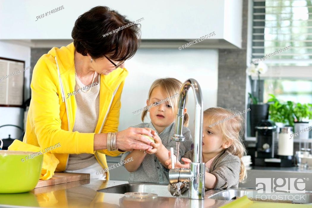 Stock Photo: Elderly woman with her granddaughters washing in a kitchen.