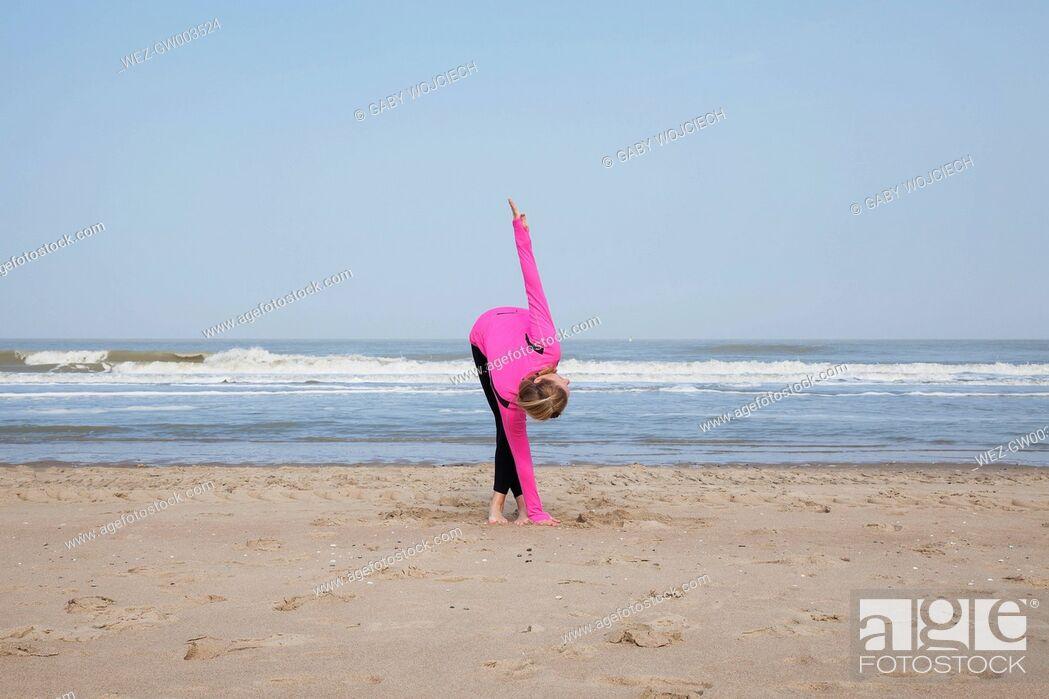 Imagen: Belgium, Flanders, woman doing yoga exercise on the beach.