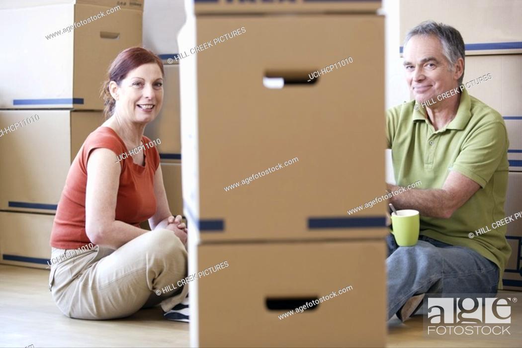 Stock Photo: Couple relaxing among cardboard boxes.