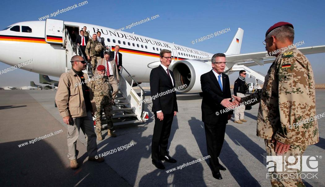 Stock Photo: German Defence Minister Thomas de Maiziere (C) and Foreign Minister Guido Westerwelle (L) are welcomed by German Bundeswehr armed forces General Joerg Vollmer.