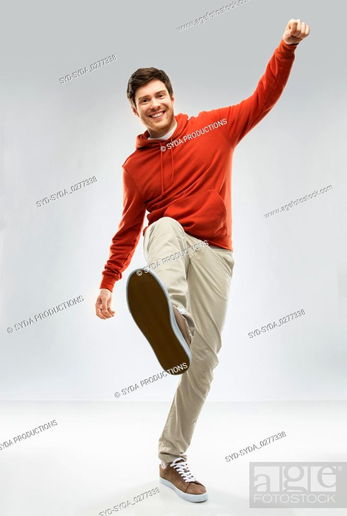Stock Photo: happy young man in hoodie stepping up.