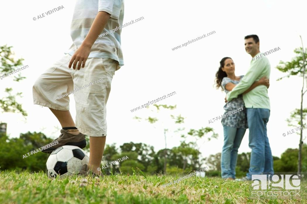 Stock Photo: Boy playing with soccer ball, parents watching and embracing in background.