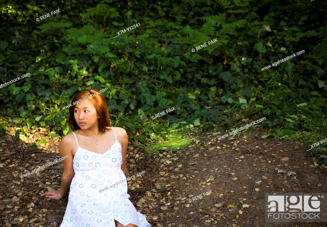 Stock Photo: Young Asian woman waiting for someone to fill the seat beside her.