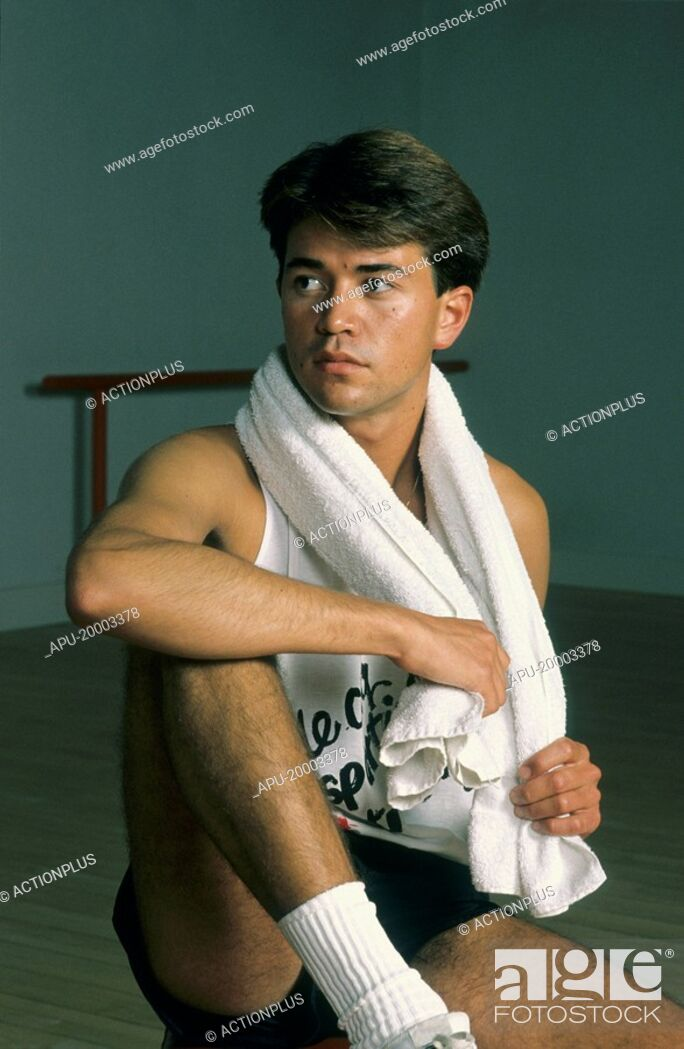 Stock Photo: Young man sitting on the floor in a gym.