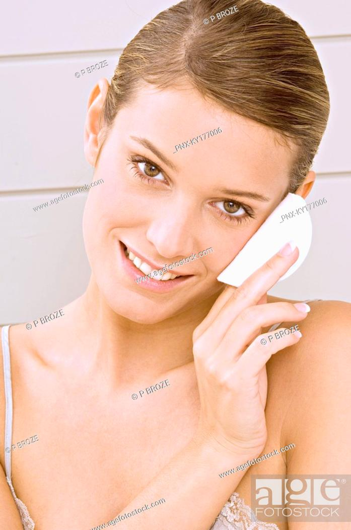 Stock Photo: Portrait of a young woman applying face powder.