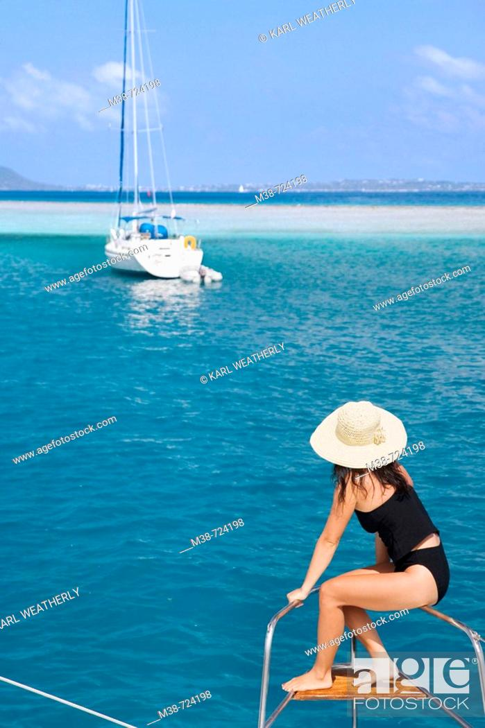 Stock Photo: Woman on the front of a sailboat, British Virgin Islands.