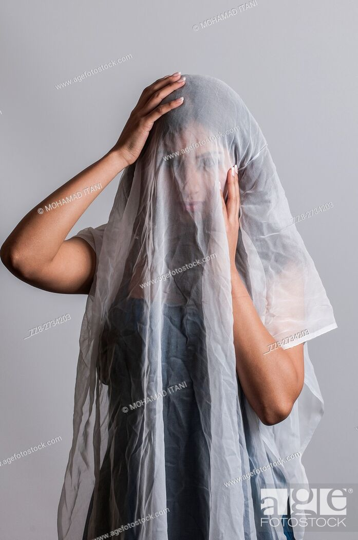Stock Photo: Woman covered with white chiffon fabric hands on head.