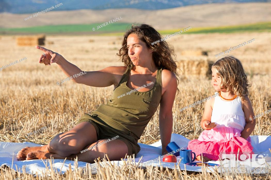 Stock Photo: mother and daughter having a picnic in the field.