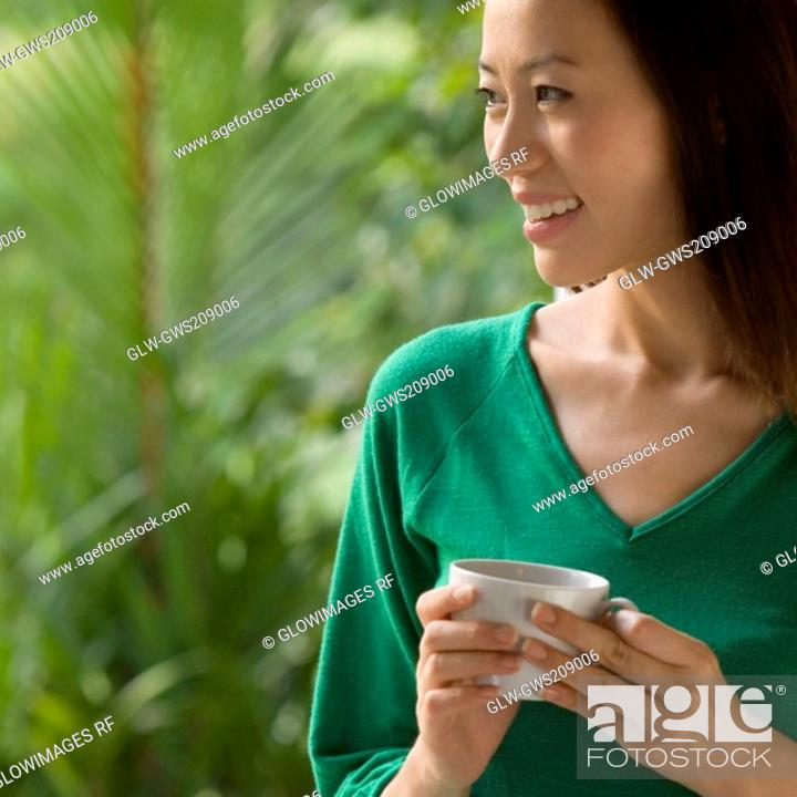 Stock Photo: Close-up of a young woman holding a cup of tea and smiling.