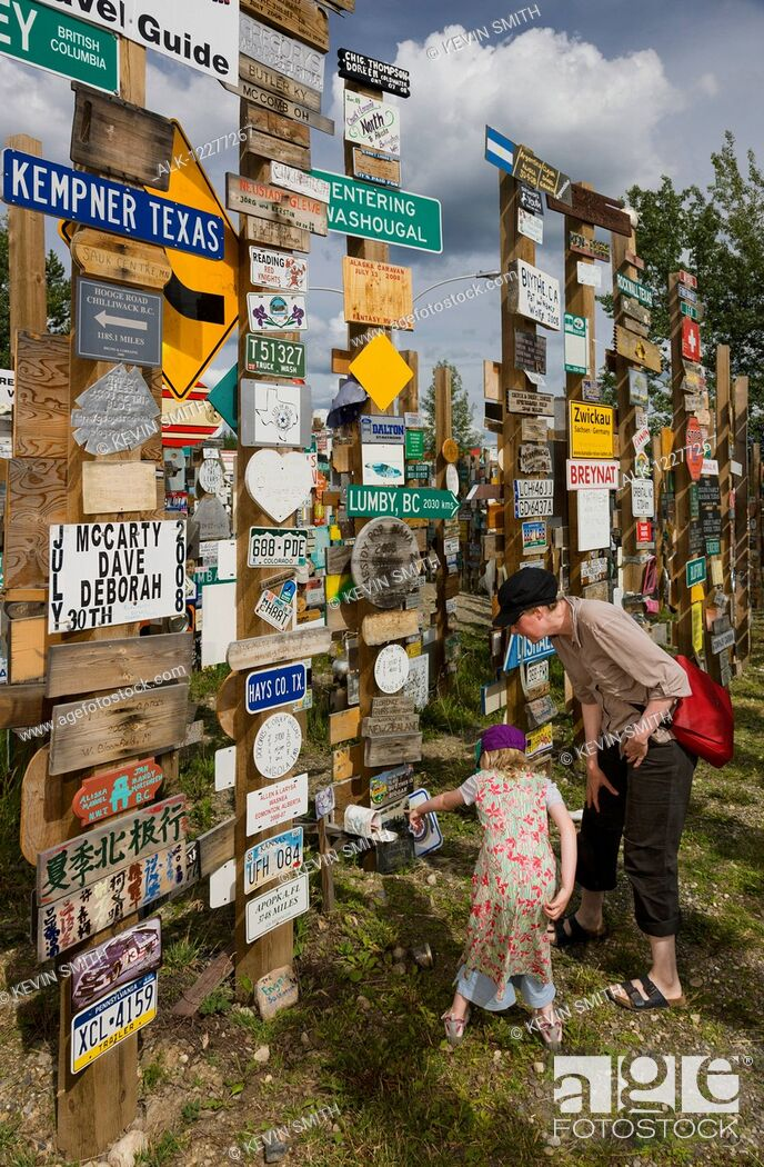 Imagen: Mother and daughter explore the Signpost Forest, Watson Lake, Yukon Territory, Canada, summer.