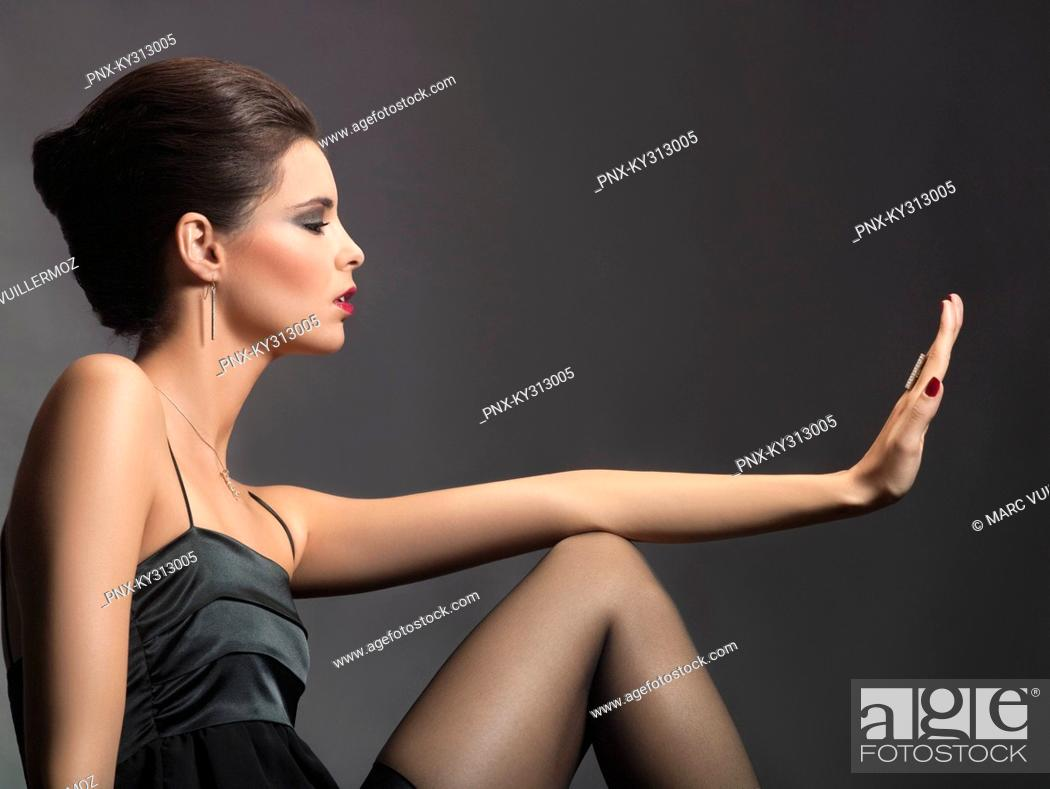 Stock Photo: Young woman looking at fingernails.
