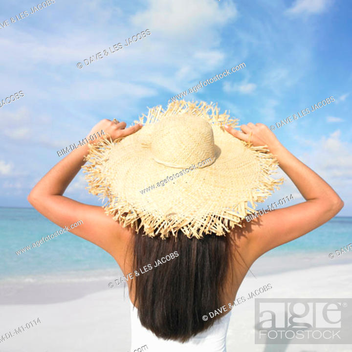 Stock Photo: Woman wearing a straw hat on the beach.