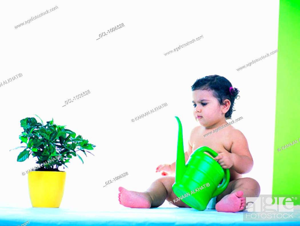Stock Photo: Toddler with watering can and indoor plant.