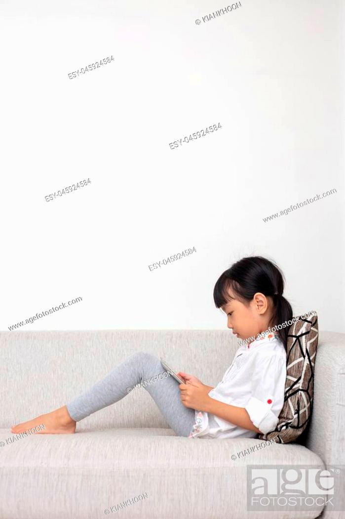 Stock Photo: Asian Chinese little girl sitting on the sofa playing digital tablet in the living room at home.