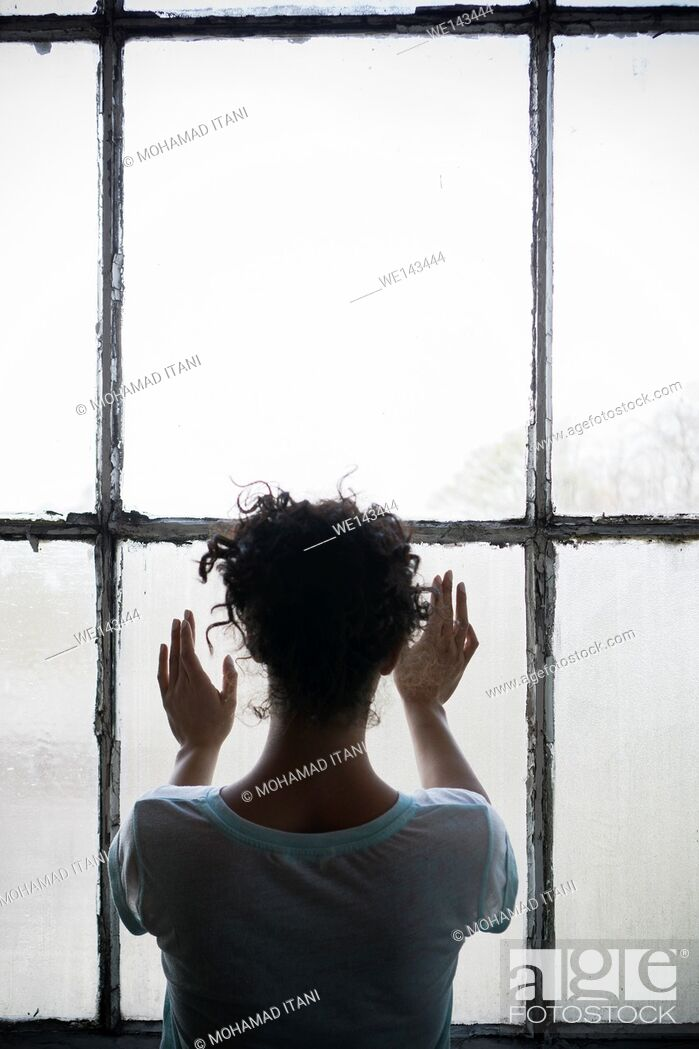 Stock Photo: Rear view of a young woman standing by the window hands touching the glass.