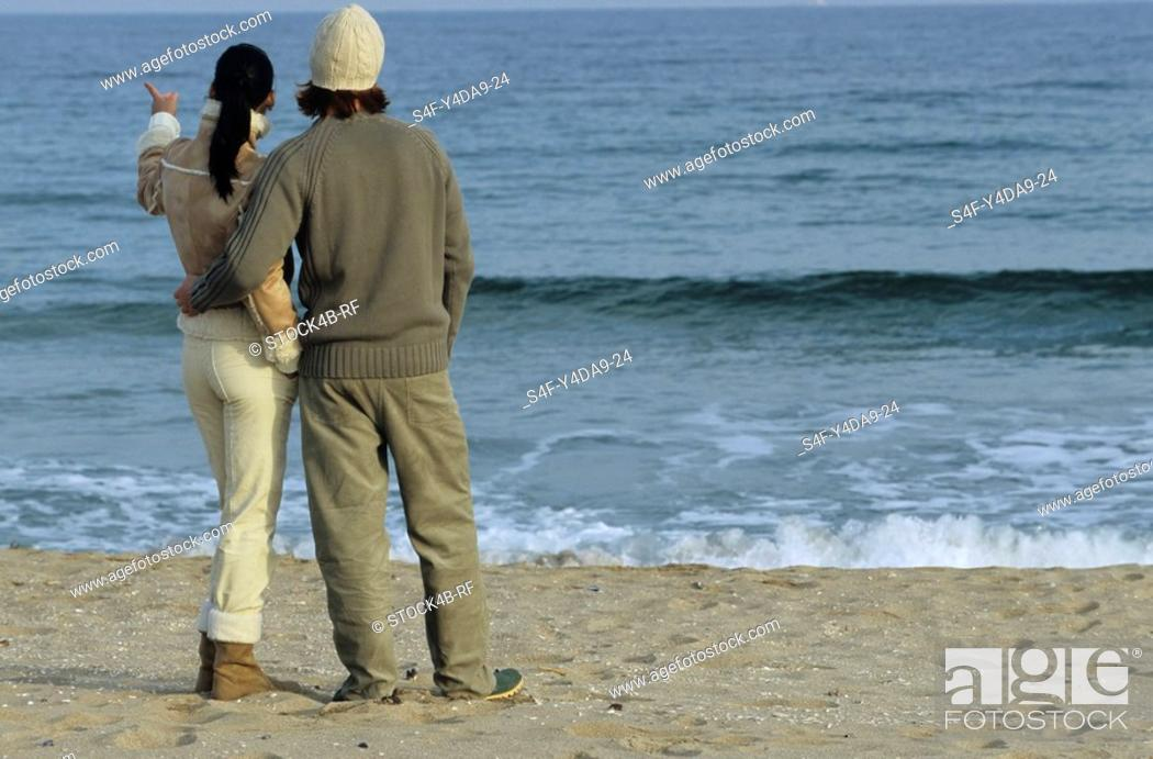 Stock Photo: Young auburn-haired Man holding a brownhaired young Woman to his Arm - Love - Togetherness - Beach.