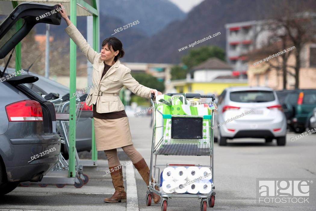 Stock Photo: A Woman Loads Her Car With Shopping Bags In A Parking Lot; Ascona, Ticino, Switzerland.