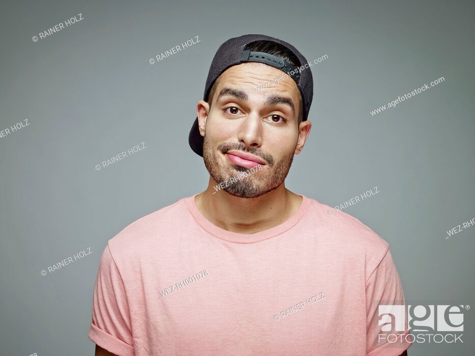 Stock Photo: Portrait of uncertain young man in front of grey background.