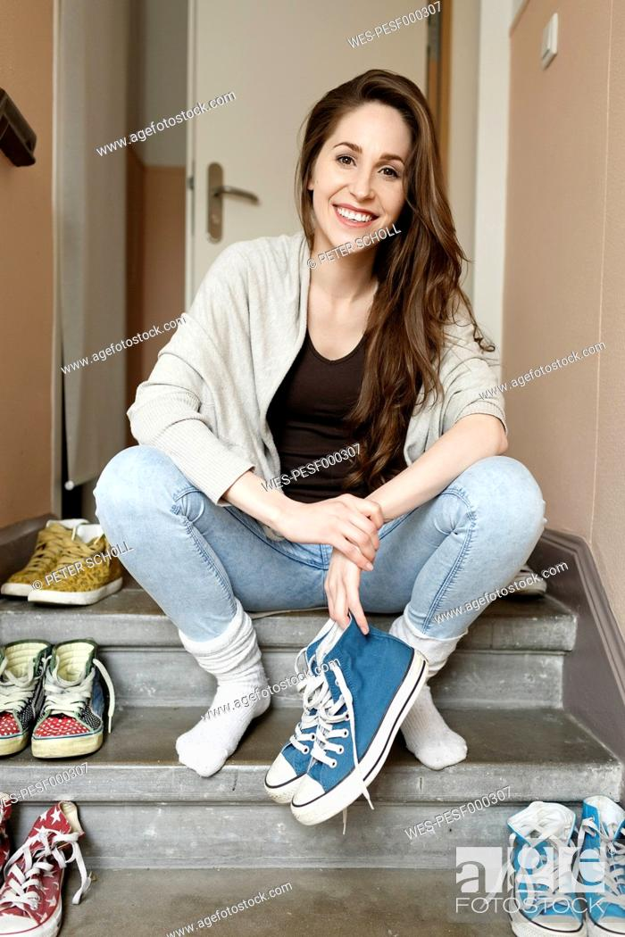 Stock Photo: Smiling young woman sitting on staircase holding sneakers.