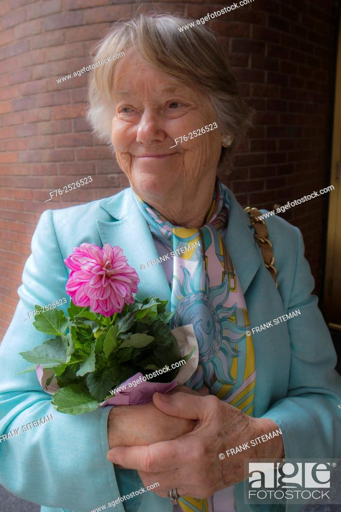 Stock Photo: Portrait of elder woman wearing silk scarf and holding a bouquet of cut flowers.
