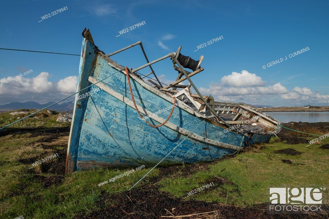 Stock Photo: Ireland, Galway, 2016/04 , A blue derelict wooden fishing boat lies decaying on the shoreline of the Irish coast.