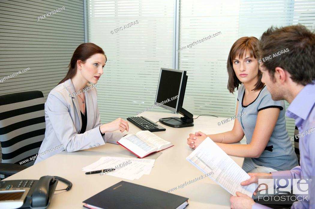 Stock Photo: Female real estate agent showing a book to a couple.