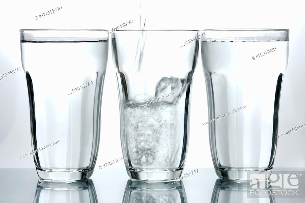 Stock Photo: Glasses of drinking water backlit against a white background.