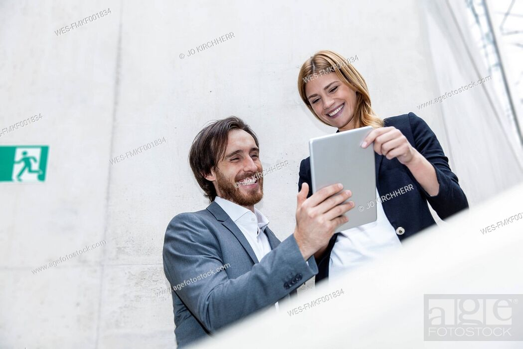 Stock Photo: Two smiling business people looking at digital tablet.