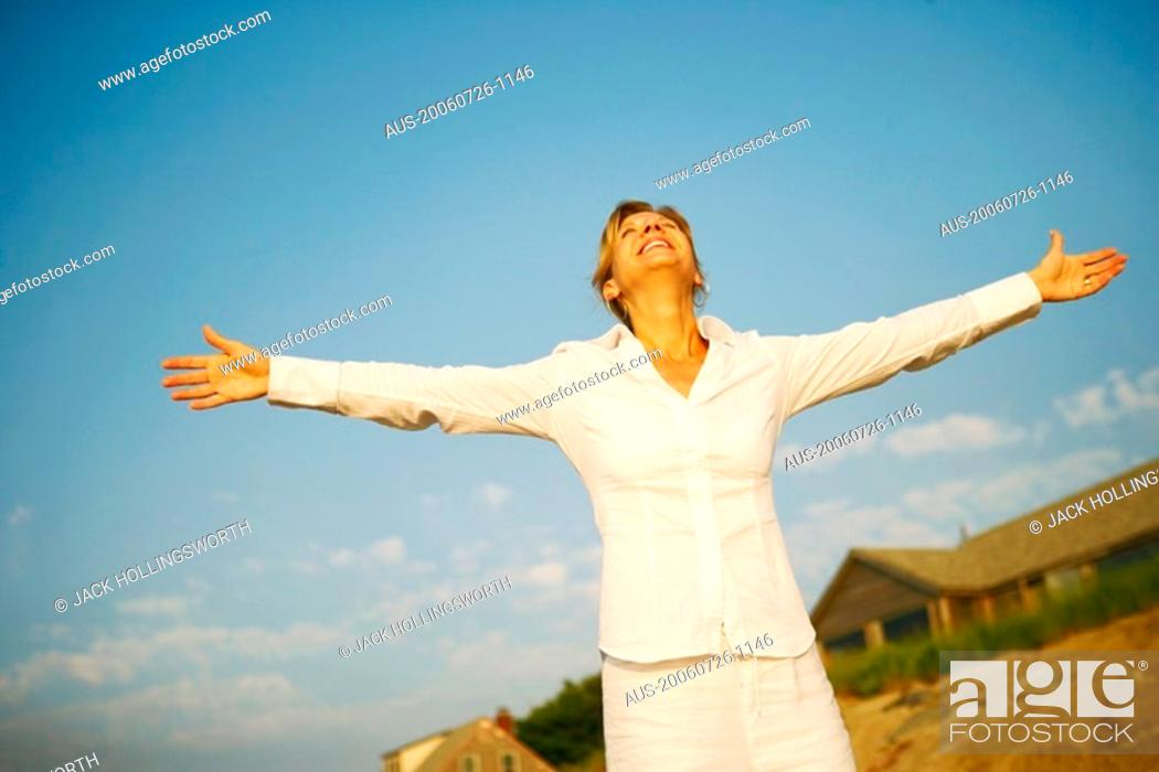 Photo de stock: Mature woman smiling with her arms outstretched.