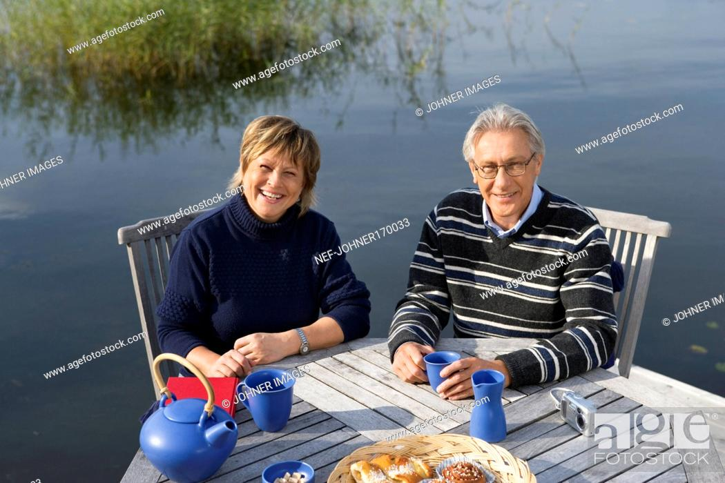 Stock Photo: A smiling couple sitting on a patio by a lake.