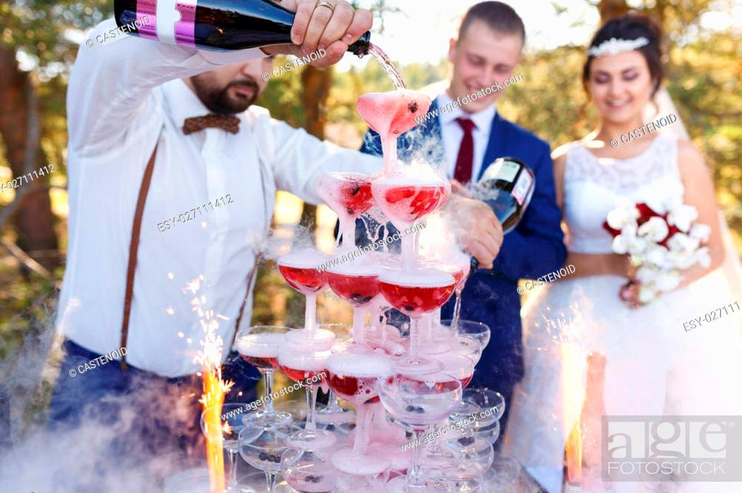 Stock Photo: Bartender with newlyweds are pouring vine in the pyramid of glasses at the open air wedding banquet.