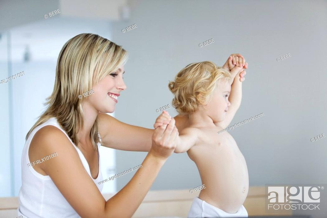 Stock Photo: Young mother with baby 12-24 months in bedroom.