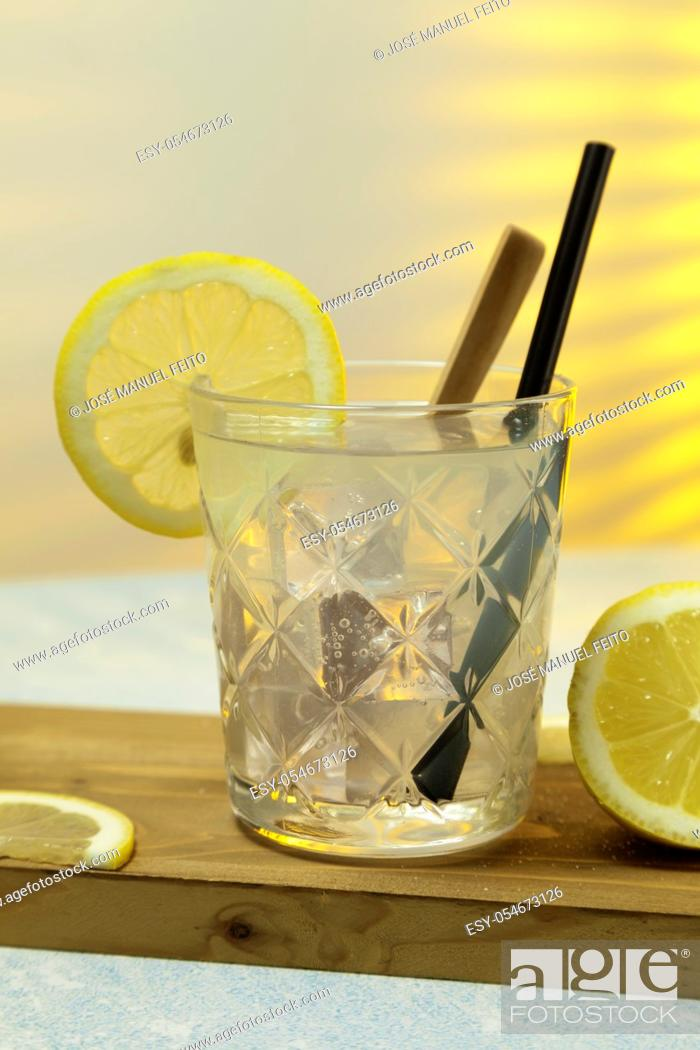 Stock Photo: close-up of refreshing lemonade glass with ice, spoon and straw on cutting board on background with sunlight entering through rear window. Copy space.