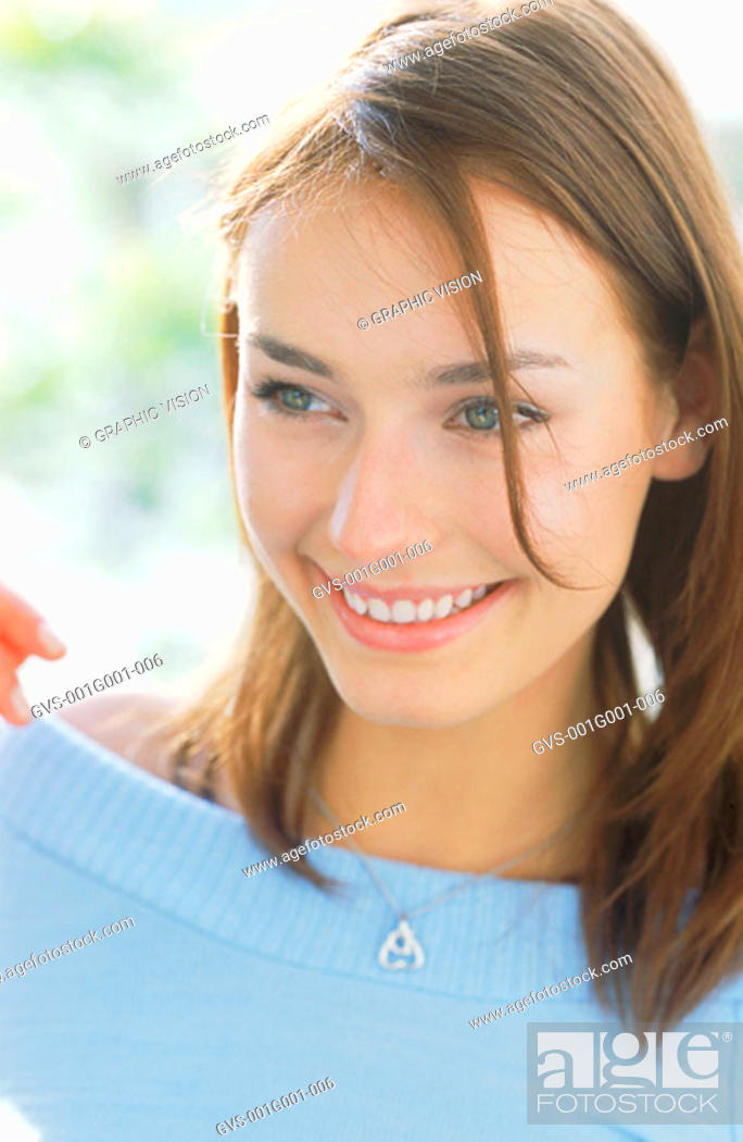 Stock Photo: Portrait of a Young Woman With Brown Hair Wearing a Blue Top.
