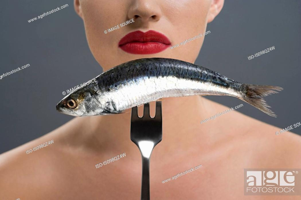Stock Photo: Woman holding a fish on a fork.