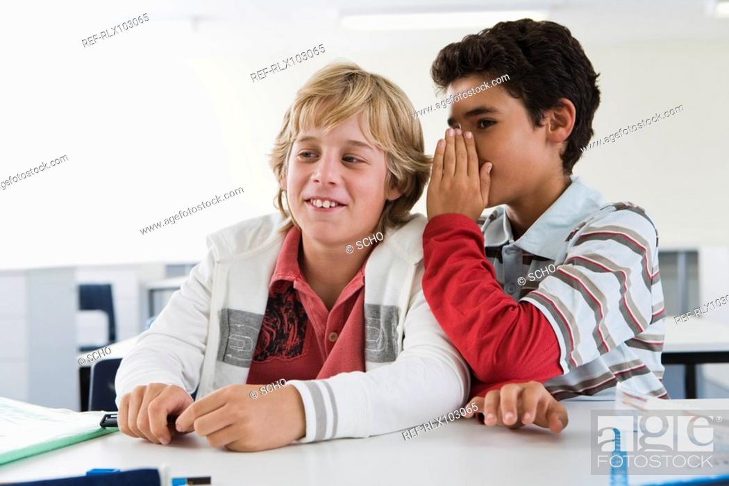 Stock Photo: Two boys 10-13 in classroom whispering, smiling.