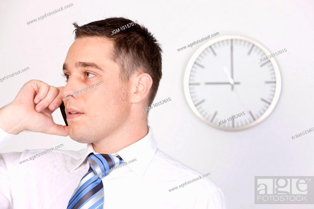 Stock Photo: Business people using mobile phone and looking away.