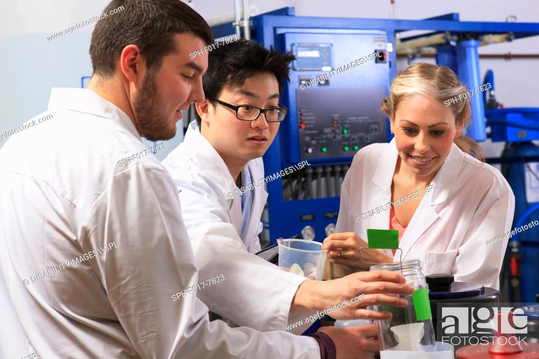 Stock Photo: Engineering students examining liquid containers in water ultra purification system room in a laboratory.