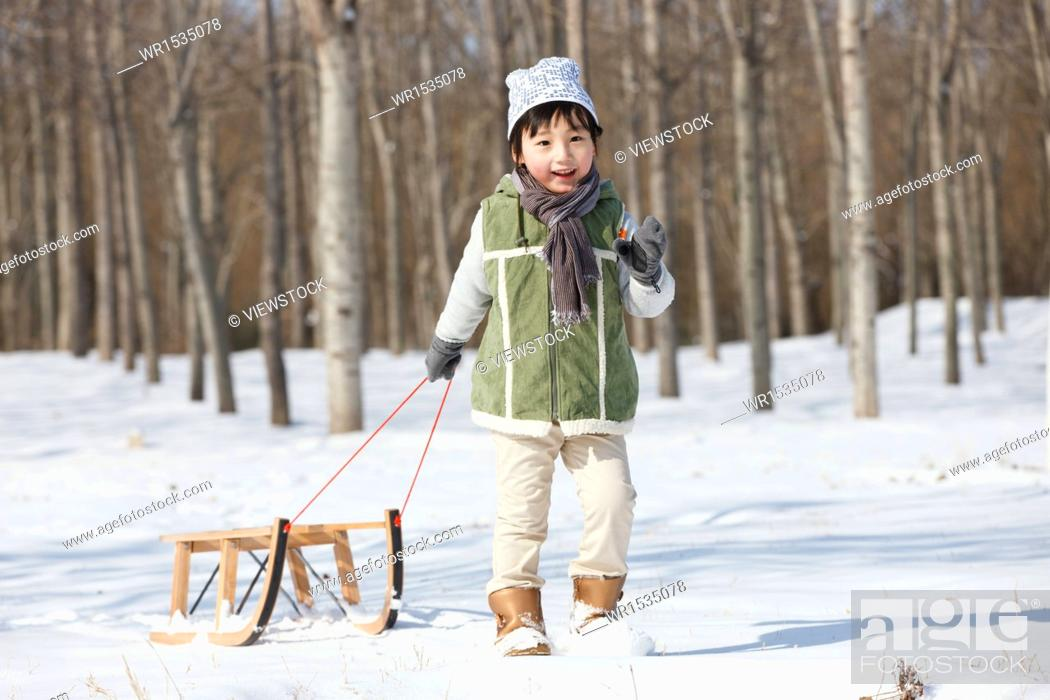 Imagen: The little boy pulled the sled in the snow.