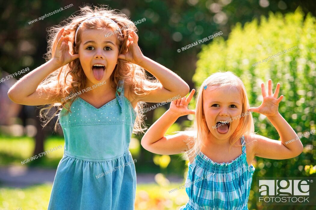 Stock Photo: Happy childhood: Little girls having fun together outdoors in park.