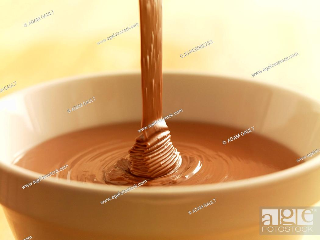 Stock Photo: Close up of chocolate syrup pouring into bowl.