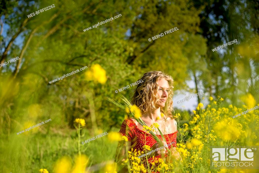Stock Photo: Thoughtful beautiful woman with curly hair standing amidst oilseed rapes.
