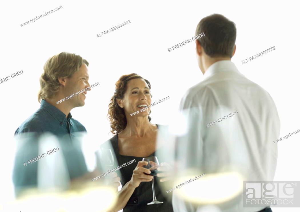 Stock Photo: Three people chatting and drinking wine.