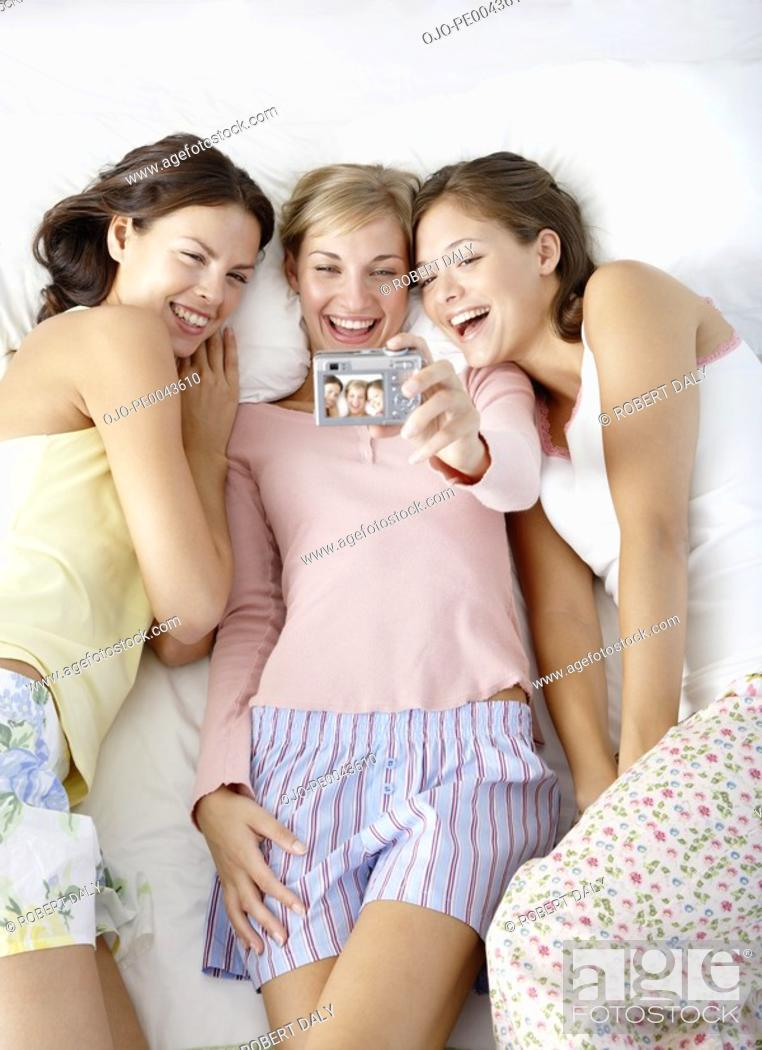 Stock Photo: Three girlfriends taking pictures.