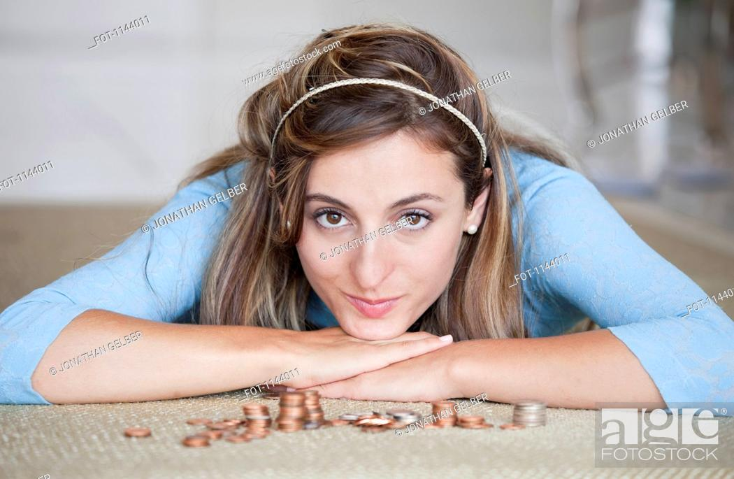 Stock Photo: A woman lying on a floor with stacks of US coins.